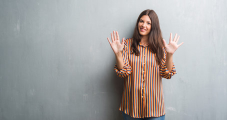Young brunette woman over grunge grey wall showing and pointing up with fingers number ten while smiling confident and happy.