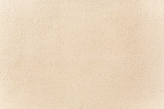 Beige stucco background. Bright wall lit by sunshine