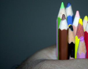 Hand holding colorful wooden pencils. Memory of childhood. Back to school.