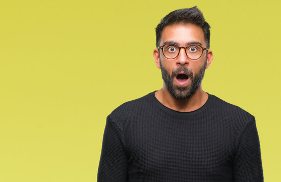 Adult hispanic man wearing glasses over isolated background afraid and shocked with surprise expression, fear and excited face.
