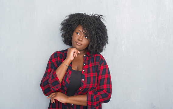 Young african american hipster woman over grey grunge wall with hand on chin thinking about question, pensive expression. Smiling with thoughtful face. Doubt concept.