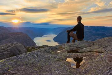 Mann sitzt auf dem Berggipfel nach vollendeter Wanderung mit Blick in Richtung Sonnenaufgang