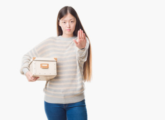 Young Chinese woman over isolated background holding a box with open hand doing stop sign with serious and confident expression, defense gesture