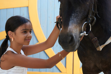 Portrait of young girl with horse. Young cute girl having fun with horse