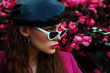 Outdoor close up fashion portrait of young beautiful woman wearing trendy  sunglasses, leather beret, earrings, fuchsia color blazer, posing near blooming pink flowers. Copy, empty space