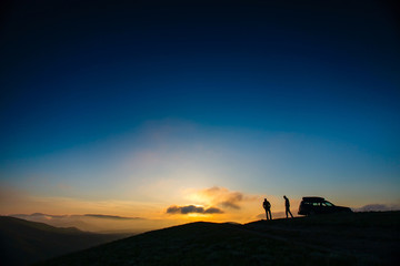 Silhouettes of two men standing on mountain top. Travelling by car