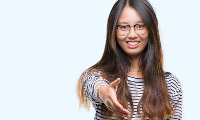 Young asian woman wearing glasses over isolated background smiling friendly offering handshake as greeting and welcoming. Successful business.