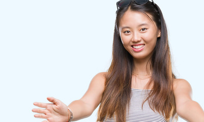 Young asian woman wearing sunglasses over isolated background looking at the camera smiling with open arms for hug. Cheerful expression embracing happiness.