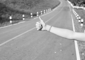 hitchhiking hand thumb road trip street woman thumb black and white alone bracelet arm