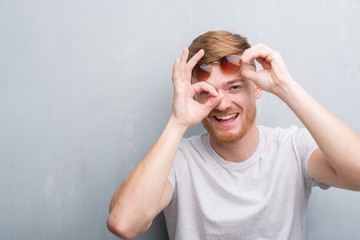 Young redhead man over grey grunge wall wearing retro sunglasses with happy face smiling doing ok sign with hand on eye looking through fingers