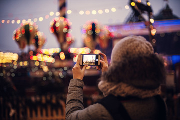 Woman Taking Pictures of European Christmas Market Scene on Smartphone