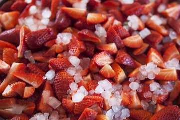 Clean strawberries cut in small pieces on ice used as an ingredient for non-alcoholic beverages or alcoholic drinks and cocktails such as gins, mojitos, sangrias, margaritas, daiquiris