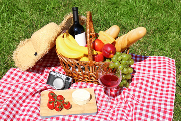 Aluminium Prints Picnic Basket with food and glass of wine on blanket prepared for picnic in park