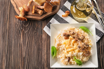 Plate with delicious risotto and mushrooms on wooden table