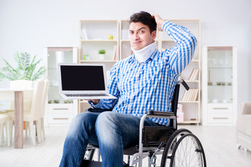 Young man suffering from injury on wheelchair at home
