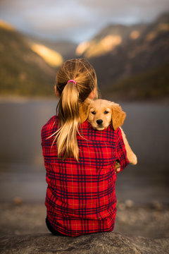 Young girl holding her golden retriever puppy dog
