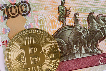 A hundred Russian ruble bank note and a gold bitcoin in macro