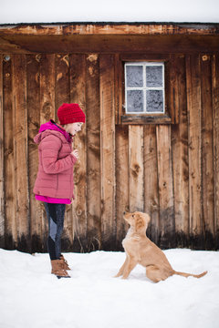 Young girl teaching her dog tricks outside in the snow