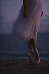 Female dancers feet on a cliff overlooking the ocean
