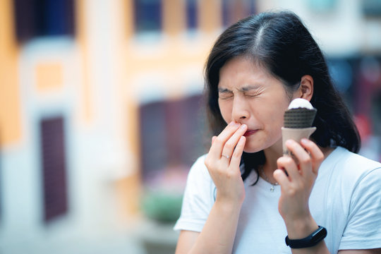 Reaction of young woman with sensitive teeth eating icecream