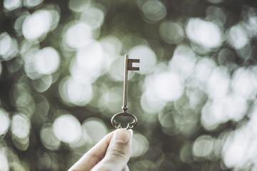 鍵を持っている手 緑ぼかし背景