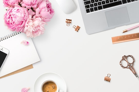 feminine workspace with laptop computer, smartphone, office supplies, a bunch of peonies and coffee on a white desk, top view / flat lay, copyspace
