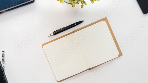 Wall mural Office desk table with pen ,plant,notebook and smart phone. Top view with copy space