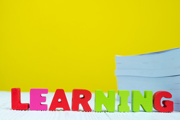 LEARNING text alphabet and pile of book on white table with yellow background.