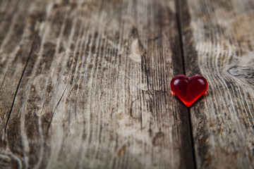 Red glass heart on a wooden background