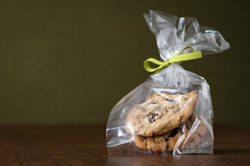 Chocolate chip cookies wrapped in a cellophane bag with green ribbon and bow on wood table with green background