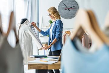 Successful fashion designer. attractive young happy casual trendy caucasian blonde fashion designer businesswoman in workshop