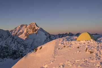 Photo sur Aluminium Pleine lune Yellow tent pitched up on a summit of a high alpine peak. Winter camping in snow covered mountains. Winter alpine landscape, climbing bivouac panorama. Vibrant blue sky, climber next to the tent.