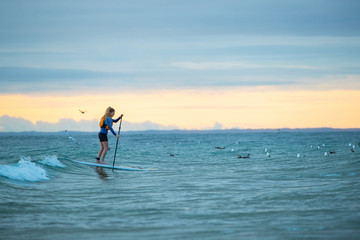 Beautiful woman stand up paddle boarding at sunrise or sunset