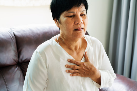 old woman having heart attack and grabbing her chest