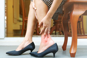 Woman leg cramp from wearing high heels shoes, healthcare concept