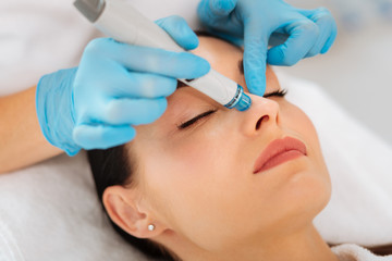 Face cleansing. Face of a nice goo looking woman during hydrafacial procedure in the beauty salon