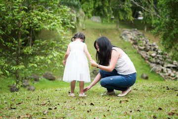 Mother helps little girl wearing shoe at park