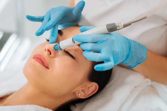 Pleasant relaxation. Beautiful young woman closing her eyes while having a hydrafacial procedure