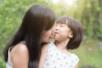 Little girl kissing mom at outdoor park