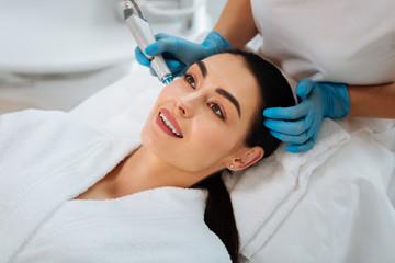 Pleasant beauty procedure. Joyful positive woman smiling while enjoying the beauty procedure
