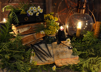 Still life with book with magic spellings, herbs, black candle and old lamp. Mystic background with ritual esoteric objects, occult, fortune telling and halloween concept