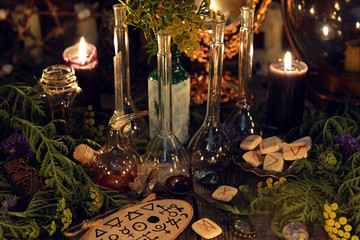 Alchemy still life with glass bottles and flask, runes, healing herbs and ritual objects. Mystic background with ritual esoteric objects, occult, fortune telling and halloween concept