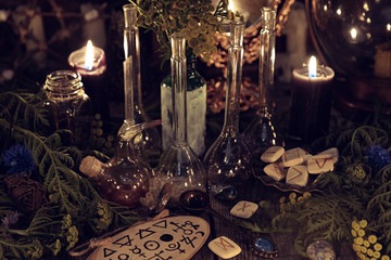 Still life with alchemy ritual objects, old bottles, herbs and black candles. Mystic background with ritual esoteric objects, occult, fortune telling and halloween concept