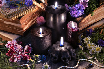 Still life with three black candles, old books, tarot cards and herbs with flowers. Mystic background with ritual esoteric objects, occult, fortune telling and halloween concept