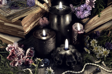 Still life with evil black candles, antique books and herbs in mystic light. Mystic background with ritual esoteric objects, occult, fortune telling and halloween concept