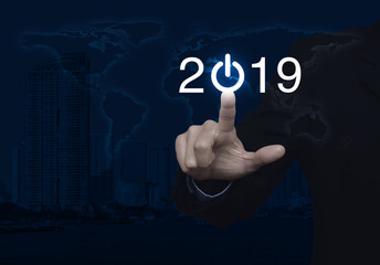 Businessman pressing 2019 start up business icon over world map and modern city tower, Happy new year concept, Elements of this image furnished by NASA