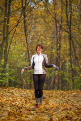 Photo of sports girl jumping with rope at autumn forest
