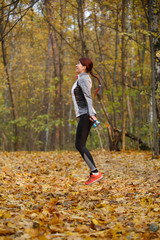 Full-length image of young brunette jumping with rope at autumn forest