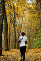 Photo from back in full growth of girl running on autumn foliage