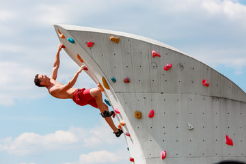 Photo of young sportsman in red shorts on wall for rock climbing against blue sky with clouds